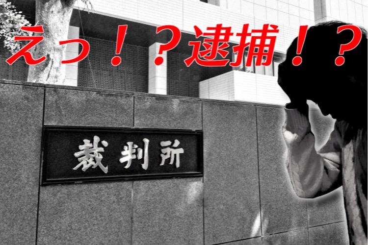 裁判所の前で頭を抱える男性