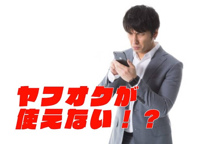 携帯を見てしかめっ面をする男性